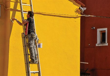Painting a yellow residential house in Henderson Nevada