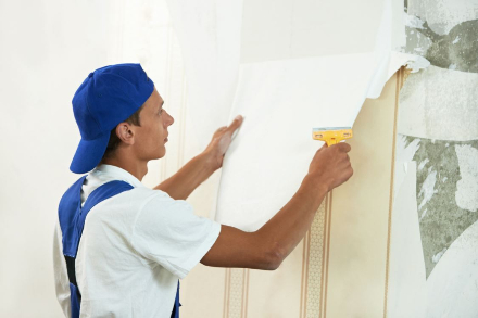 Man removing wallpaper to prep for interior residential painting in Henderson Nevada